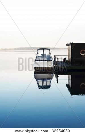 Boat And Houseboat On Calm Morning Lake.