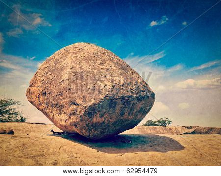 Vintage retro hipster style travel image of Krishna's butterball -  balancing giant natural rock stone with grunge texture overlaid. Mahabalipuram, Tamil Nadu, India