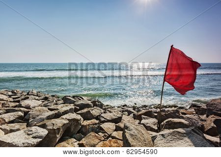 Danger - Red flag on rocky beach forbidding to swim
