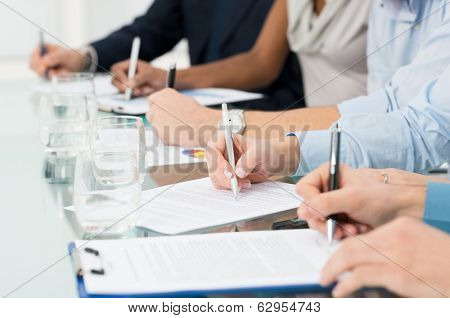 Closeup Of Businesspeople Hand Over Paper Taking Notes At Seminar