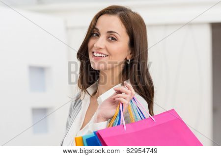 Portrait Of Happy Young Woman Carrying Shopping Bags