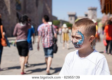 Boy painting face with shark in amusement park.