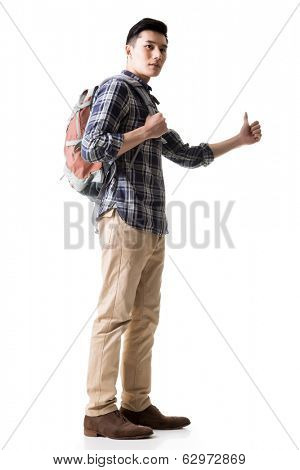 Asian young traveling man hitchhiking, full length portrait isolated on white.