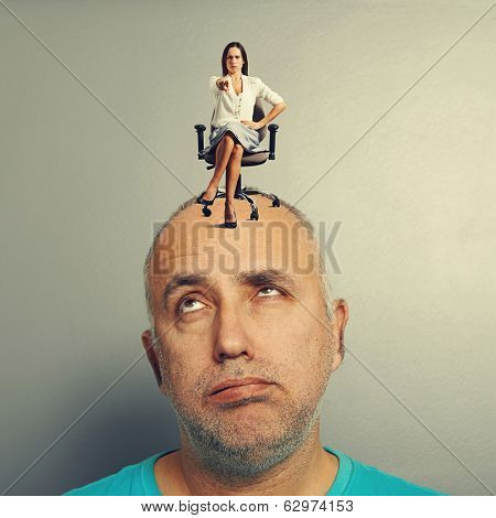 strict woman sitting at tired man and pointing