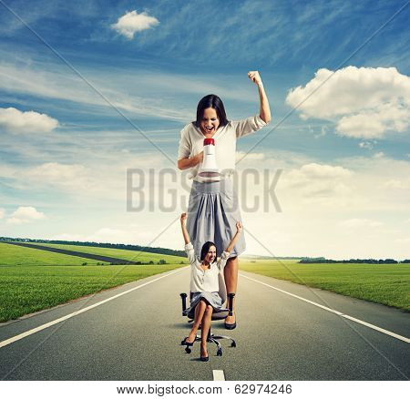 aggressive woman with megaphone reproaching joyful small woman on the road