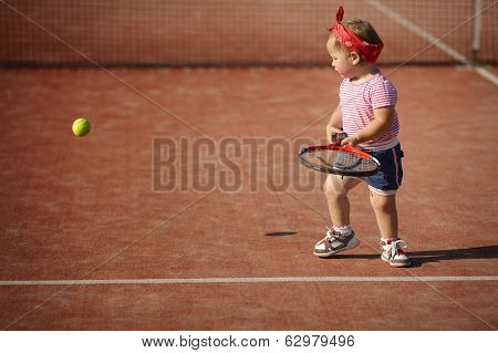 little girl plays tennis