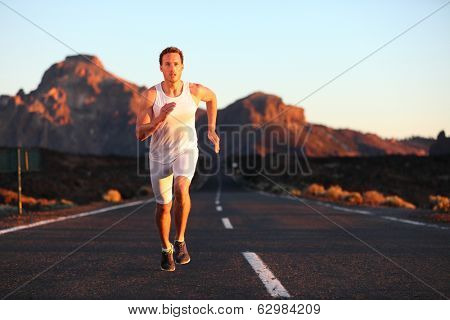 Athlete running sprinting at sunset on road. Male runner training in mountain landscape at night. Fit young muscular fitness sport model in his 20s.