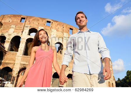 Couple in Rome by Colosseum walking holding hands in Italy. Happy lovers on honeymoon sightseeing having fun in front of Coliseum. Love and travel concept with multiracial couple.