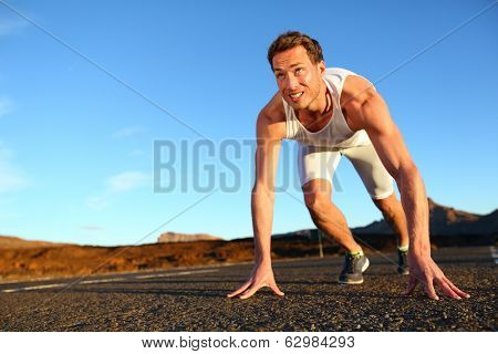 Sprinter starting sprint - man running getting ready to start sprinting run. Fit male runner athlete training outside on road in beautiful mountain landscape nature.