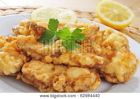 closeup of a plate with spanish rape rebozado, battered and fried angler