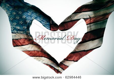 memorial day written in the blank space of a heart sign made with the hands patterned with the colors and the stars of the United States flag