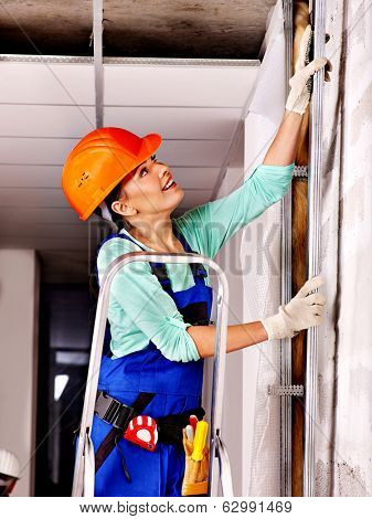 Happy woman in builder uniform indoor.