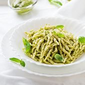 stock photo of pesto sauce  - Italian traditional pasta trofie al pesto on the wooden table selective focus and square image - JPG