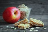 stock photo of roughage  - Apple granola barre with fruits and oat in background - JPG