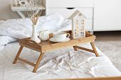 stock photo of bed breakfast  - Wooden tray with coffee and interior decor on the bed with white linen - JPG