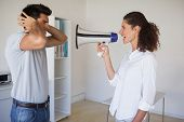 Casual businesswoman shouting at colleague through megaphone in the office