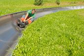 stock photo of luge  - Happy young man enjoying alpine coaster luge during summer - JPG