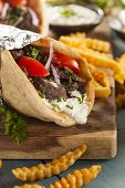stock photo of gyro  - Homemade Meat Gyro with Tzatziki Sauce tomatos and French Fries