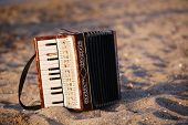 image of accordion  - Accordian standing on the sand on a beach conceptual of bohemian country music and entertainment - JPG