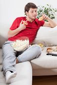 stock photo of couch potato  - Couch potato eating junk food during watching tv - JPG