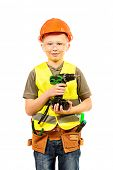 Boy in a helmet plays in the builder with tools. Isolated