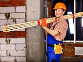Happy man in builder uniform carry boards indoor.