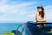 stock photo of recreational vehicle  - Relaxed happy woman on summer travel vacation to the coast leaning out car sunroof with the sea on background.
