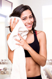 stock photo of transpiration  - Fitness woman wiping sweat with a towel