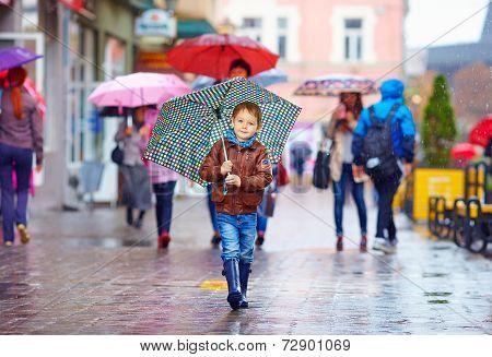 Cute Boy With Umbrella Walking On Crowded City Street