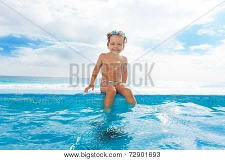 Smiling boy sitting on stoned boarder near water