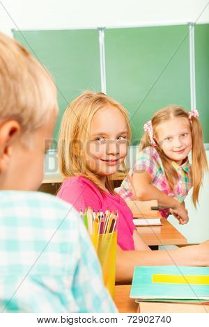 Beautiful girl looks at boy while turned sitting
