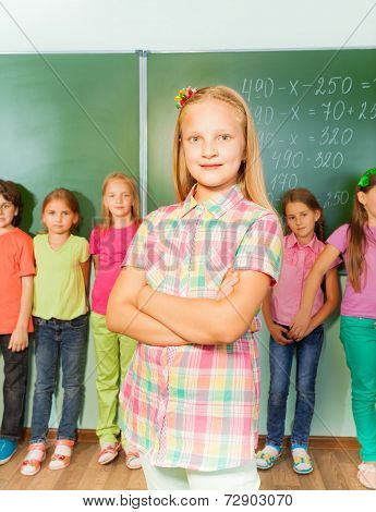Smiling girl with arms crossed near chalkboard