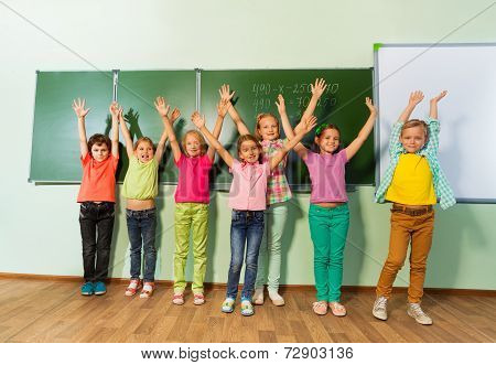 Kids stand with arms up in line near blackboard