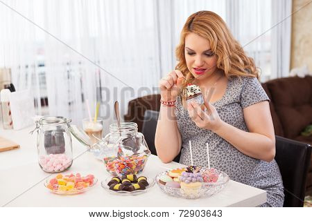 Pregnant Young Woman Eating Sweets