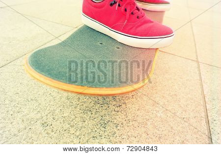 skateboard and sneakers at skatepark