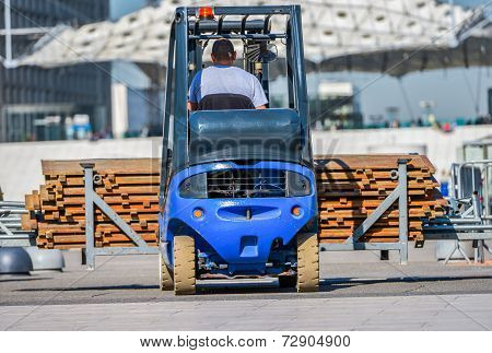 A Construction Worker Driving A Blue Construction Machine