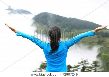 cheering hiking woman enjoy the beautiful view at mountain peak