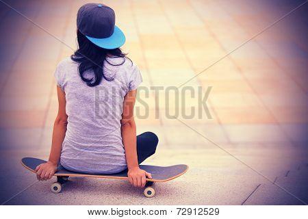 woman skateboarder sit on skateboard outdoor