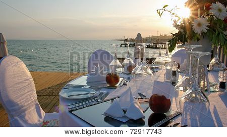 Romantic Table Setting On Pier At Sunset