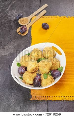 Plum dumplings in bowl on table