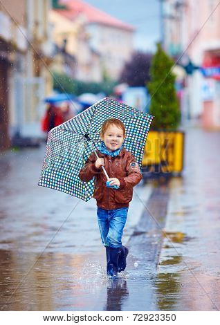 Cute Kid, Boy Walking In Puddle In Rainy City
