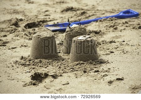 Three Simple Sandcastles with Blue Spade