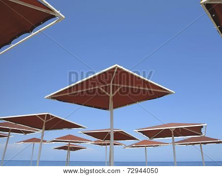Red Metallic Parasol Beach Umbrellas Over Blue Sky