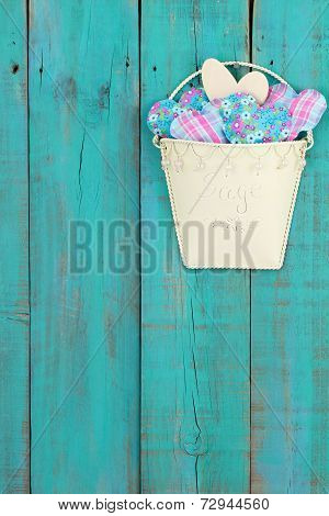 Tin pot of country hearts hanging on antique teal blue distressed wood fence