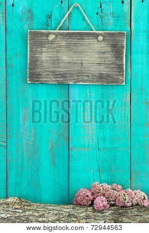 Blank rustic sign hanging on antique teal blue wood fence with log and pink flower border