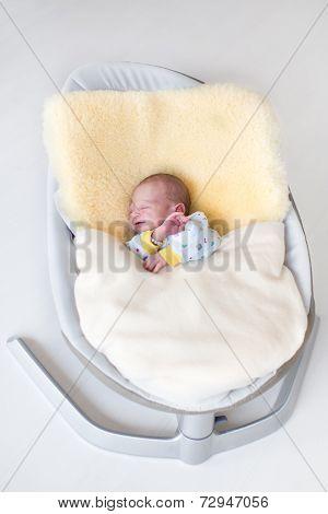 Sweet Newborn Baby Boy Sleeping In A Swing On A Sheepskin Under A Warm Knitted Blanket