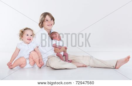 Portrait Of Three Siblings, School Age Boy, His Toddler Sister And A Newborn Baby Brother
