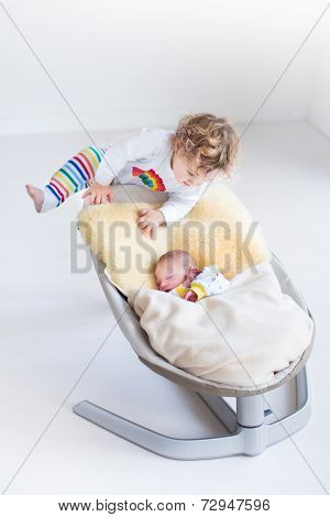 Cute little toddler girl climbing on a swing with her newborn baby brother