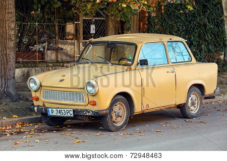 Old Yellow Trabant 601S Car Stands Parked On A Street Side