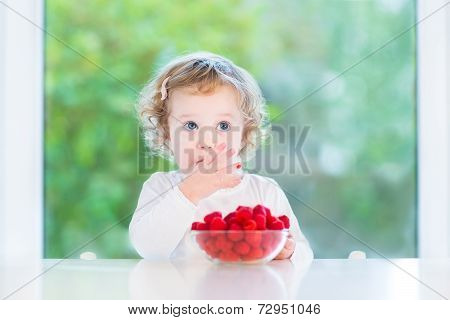 Cute Toddler Girl Eating Raspberry At A White Table Next To A Big Window
